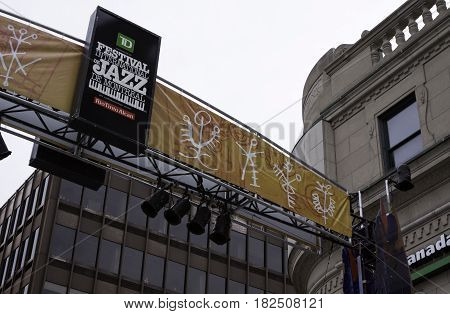 Montreal, Quebec - June 27, 2015 - Wide view of a Jazz Festival sign on a banner with lights hanging on the overhead framework attached to an old corner building in downtown Montreal, Quebec on a bright day at the end of June.