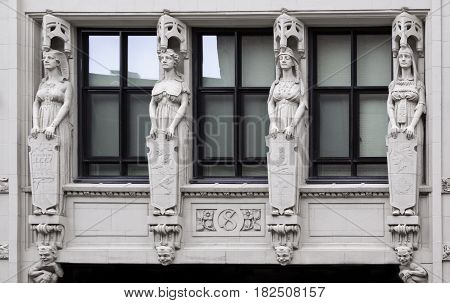 Montreal, Quebec - June 27, 2015 - Wide view of four carved statues on a building in downtown Montreal, Quebec slightly on a bright day at the end of June.