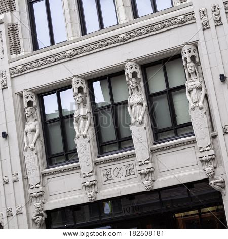 Montreal, Quebec - June 27, 2015 - Square view of four carved statues on a building in downtown Montreal, Quebec, slightly skewed for dramatic effect, on a bright day at the end of June.