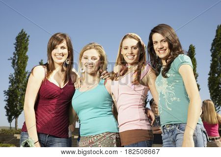 Four teenaged girls smiling outdoors