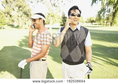 Two men talking on cell phones at golf course