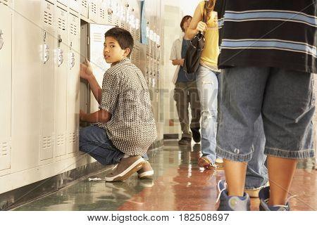 Asian boy using locker at school