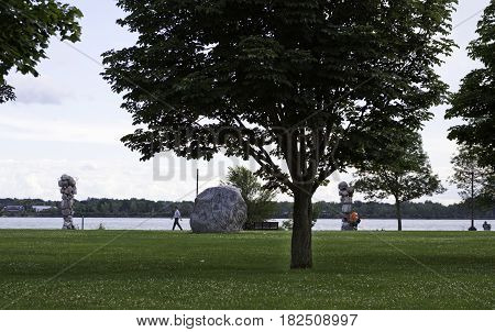 Lachine, Quebec - August 1, 2015 -- Wide view of people walking by the sculptured and carved rock displays by the Lachine Canal in Rene Levesque Park, Lachine, Quebec on a sunny day in August.
