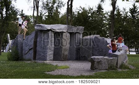 Lachine, Quebec - August 1, 2015 -- Wide view of children playing on a carved rock display in Rene Levesque Park, Lachine, Quebec on a sunny day in August.