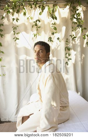 African man in bathrobe sitting on spa table