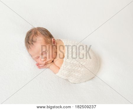 Adorable child napping covered with scarf, hairy little infant, hands under cheek
