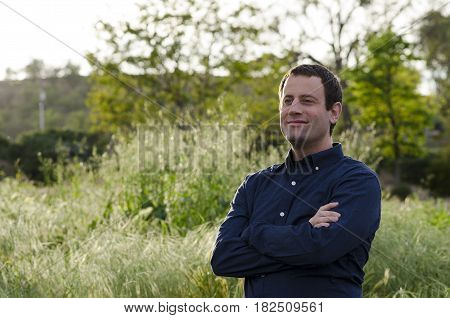 Smiling man looking forward to the future in a grassy field with arms crossed.