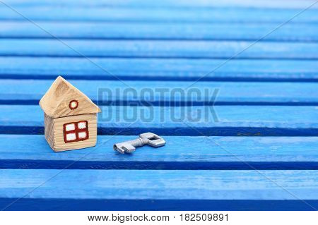 small wooden house with a key on a blue wooden surface / turnkey solution for individual accommodation