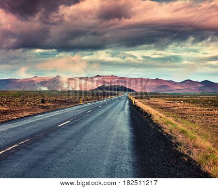 Empty asphalt road with colorful cloudy sky. Beautiful outdoor scenery in the Hverarond geothermal valley Iceland Europe. Image of travel concept background