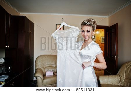 Blonde Bride On Silk Robe With Wedding Dress On Hangers. Morning Bride.