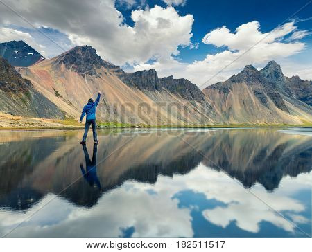 Walking upon the waters surface on the Stokksnes headland on the southeastern Icelandic coast. Man standing on the midle of lake with raised hand and enjoying moment. Iceland Europe.