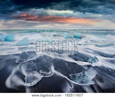 Blocks of ice washed by the waves on Jokulsarlon beach. Dramatic summer sunrise in Vatnajokull National Park southeast Iceland Europe.Artistic style post processed photo.
