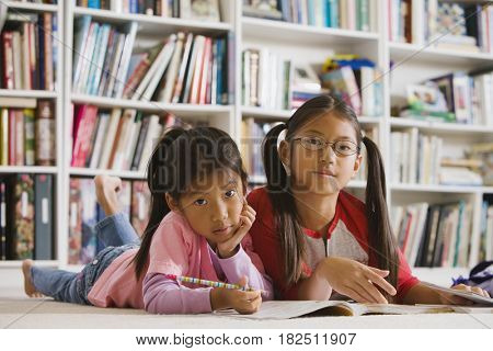 Asian sisters doing homework in library