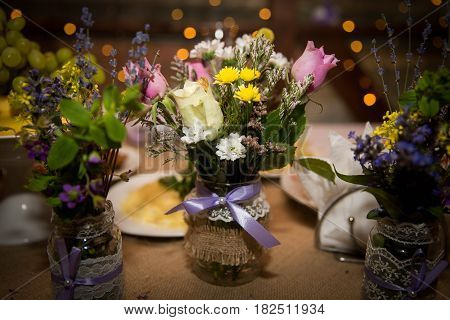 Decorative fresh bouquets of roses and wildflowers in designer bottles.