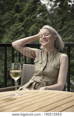 Middle-aged woman with glass of wine on patio