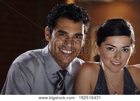Hispanic couple smiling and dressed for a night out