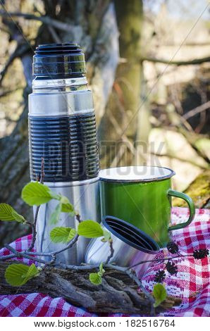 thermos and a cup used in nature