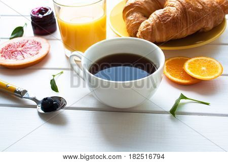 A cup of coffee and croissants on a white wooden table