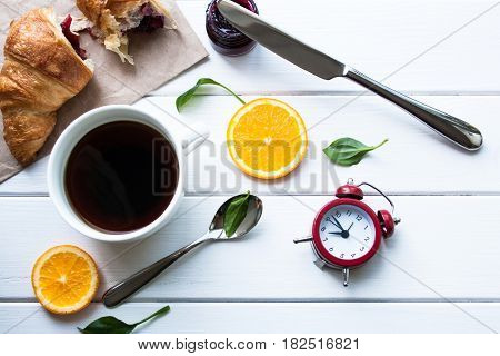 Croissants coffee and alarm clock on a white wooden table