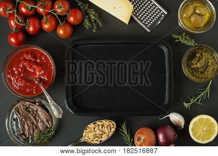Fresh vegetables and ingredients for cooking pasta on black background place for text. Vegan food vegetarian and healthy cooking concept.