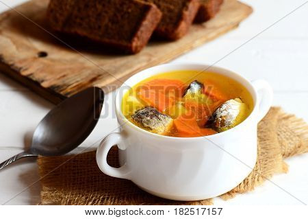 Hearty vegetable fish soup. Delicious slow fish soup with potatoes and carrots in a bowl, rye bread slices, spoon on wooden table. Closeup