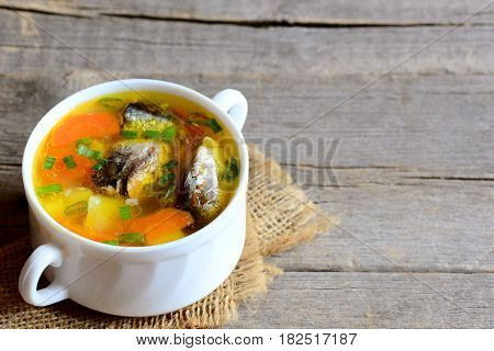 Hearty and slow fish soup. Homemade fish soup with vegetables in a bowl. Vintage wooden background with copy space for text. Closeup