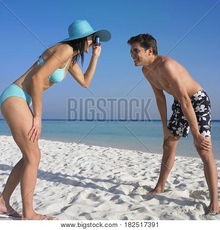 Woman taking boyfriend's photograph at beach