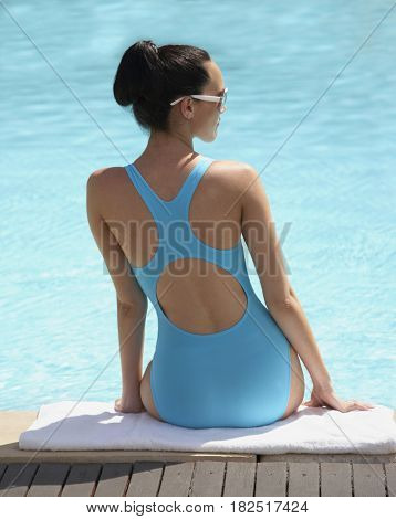 Pacific Islander woman sitting next to swimming pool