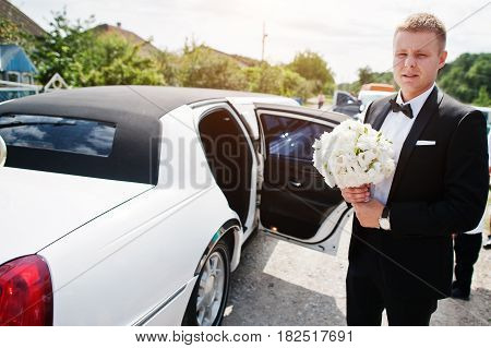 Stylish Groom With Wedding Bouquet At Hands Near Limousine.