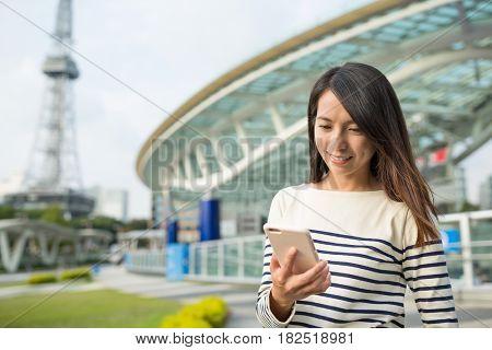 Woman using smart phone in Nagoya city
