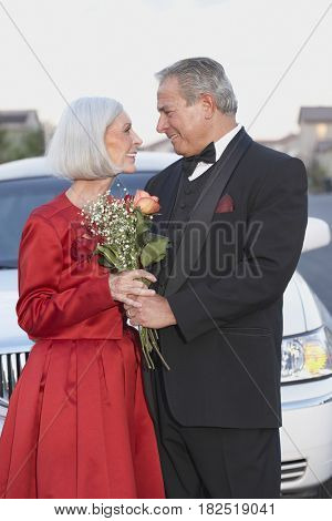 Senior couple in formal wear smiling at each other