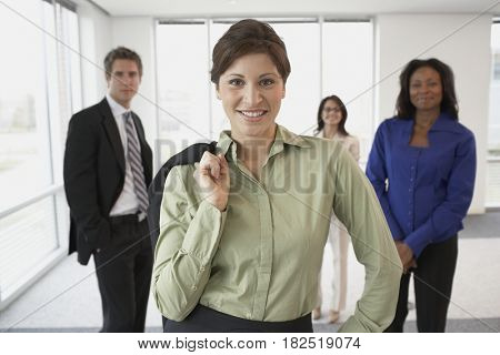 Hispanic businesswoman with co-workers in background