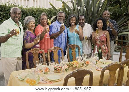 Senior African couples toasting at dinner party