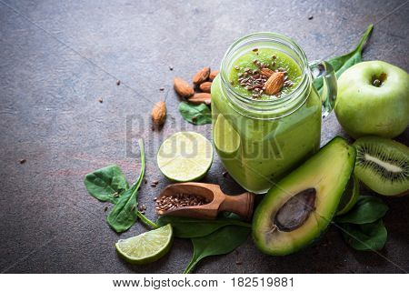 Green apple avocado and spinach smoothie with flax seeds and nuts in mason jar. Healthy food and detox.