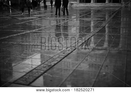 Reflection of people and buildings on the sidewalk tile after the rain.