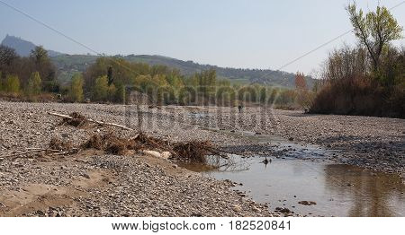 Channel of a dried-up river and trees around.