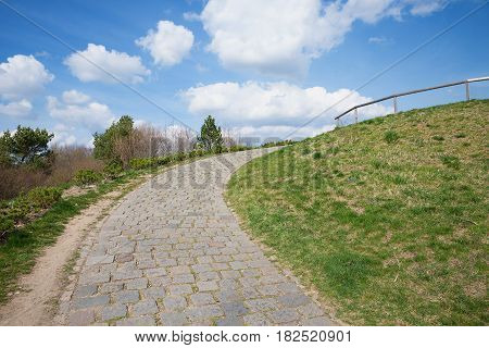 paved walkway up the hill with curve. blue sky with clouds.