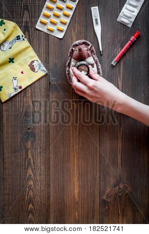 children's doctor work with stethoscope and toys on wooden desk background top view space for text