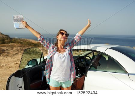 Joyful young woman with a map in her hand traveling on a cabriolet