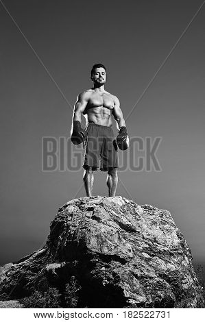 Low angle monochrome shot of a strong confident fighter wearing boxing gloves looking fiercely to the camera standing on top of a rock muscular body torso healthy lifestyle achievement power.