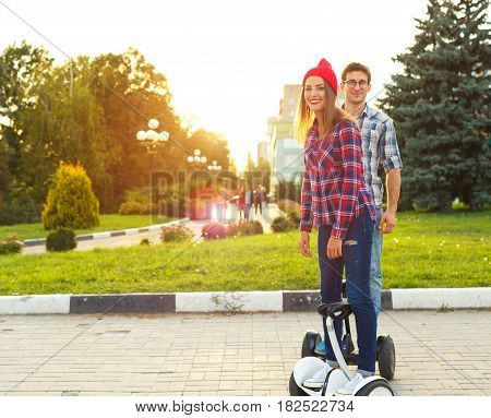 Young couple riding hoverboard - electrical scooter personal eco transport gyro scooter smart balance wheel. New modern technologies