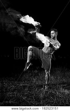 Monochrome shot of a shirtless muscular strong young male boxer practicing outdoors with his boxing gloves flaming with fire burning burn fiery force confidence martial combat fit muscles sweat agile.