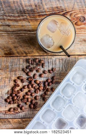 coffee break with cold iced latte and beans in caffee on wooden table background top view