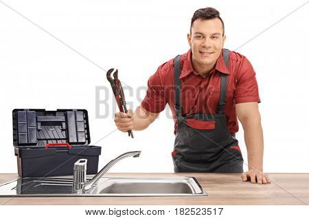 Plumber with a pipe wrench and a toolbox standing behind a sink and looking at the camera isolated on white background