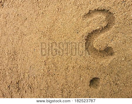 question mark drawn in the sand at the beach