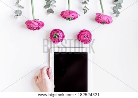 Modern spring design with bright pink flowers and tablet in hand on white desk background top view moke up