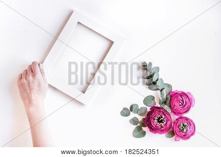 Modern spring design with bright pink flowers, hand and frame on white desk background top view moke up