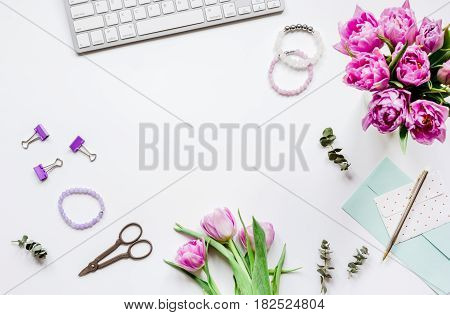 Work desk with spring flowers in home office concept on white background top view space for text