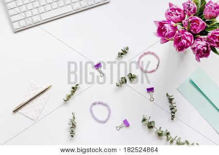 Spring flowers on trendy woman desk in office place on white background top view