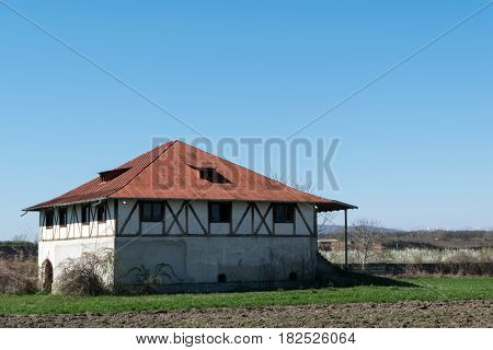 single plain house with interesting wood beams walls and hills in the background. exterior photograph